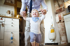Unrecognizable father holding hands of his son taking first steps. Stock Photo