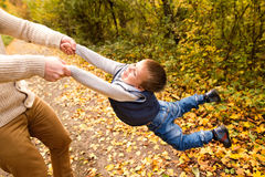 Unrecognizable father with son, spinning him. Autumn nature. Stock Photos