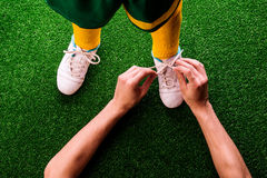 Unrecognizable father tying shoelaces to his son, football. Legs of unrecognizable little football player in yellow knee socks with soccer, having his shoelaces royalty free stock image