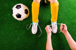 Unrecognizable father tying shoelaces to his son, football player. Legs of unrecognizable little football player in yellow knee socks with soccer ball having his stock photography