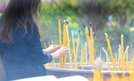 Unrecognizable Buddhist Worshipper pray and planting incense sticks at the altar. Smoke from incense in the foreground. stock image