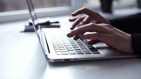 Unrecognizable female hands with accurate manicure typing something on laptop keyboard.  stock video footage