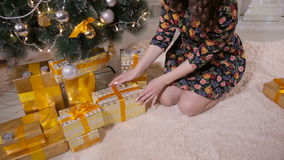Unrecognizable female hands put gifts under the Christmas tree. Christmas celebration concept. stock footage