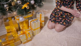 Unrecognizable female hands put gifts under the Christmas tree. Christmas celebration concept. stock video footage