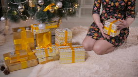 Unrecognizable female hands put gifts under the Christmas tree. Christmas celebration concept. stock video