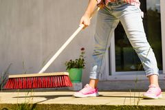Woman using broom to clean up backyard patio. Unrecognizable female person using big broom to clean up backyard patio Royalty Free Stock Photos
