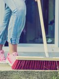 Woman using broom to clean up backyard patio. Unrecognizable female person using big broom to clean up backyard patio stock photography
