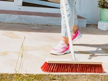 Woman using broom to clean up backyard patio. Unrecognizable female person using big broom to clean up backyard patio stock photos