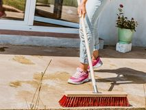 Woman using broom to clean up backyard patio. Unrecognizable female person using big broom to clean up backyard patio stock photo