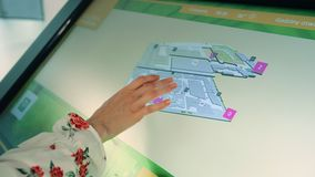 Unrecognizable female searching for right way while using on digital navigation board in mall. stock video footage