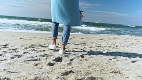Unrecognizable female in sky blue coat, jeans and shoes walk alone on beach with white sand at autumn sunny day.
