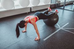 Anonymous woman doing plank on ball stock photos