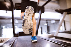 Unrecognizable fit hispanic man in gym running on treadmill. Unrecognizable fitness man in gym doing cardio workout, exercising on treadmill. Close up of sole stock photo