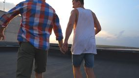 Unrecognizable gay couple standing on roof and rejoices life with cityscape at background. Friends raising hands showing. Joyful emotions. Men at rooftop and stock video footage