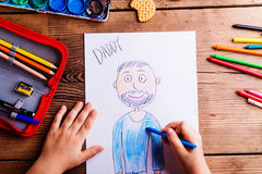 Unrecognizable girl drawing picture of her father. Wooden backgr Stock Images