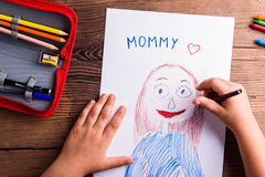 Unrecognizable girl drawing picture of her mother. Wooden backgr Royalty Free Stock Photo