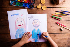 Unrecognizable girl drawing pictures of her mother and father. Hands of unrecognizable child drawing pictures of her mother and father. Studio shot on wooden Royalty Free Stock Images
