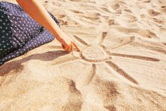Girl draws a sun with sunbeams on sand beach. stock image