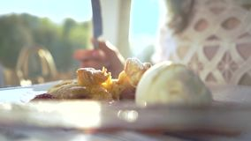 Unrecognizable girl eating steaming hot dessert at the restaurant. Clip stock footage