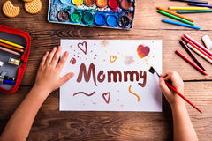Unrecognizable girl painting picture for her mom, Mothers day Stock Photo