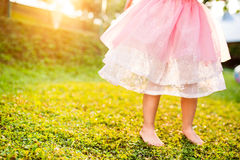 Unrecognizable girl in princess skirt running in sunny garden Royalty Free Stock Photo