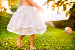 Unrecognizable girl in princess skirt running in sunny garden Stock Photography