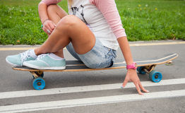 Unrecognizable girl sitting on a longboard Royalty Free Stock Image