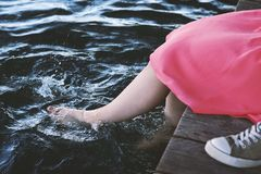 Unrecognizable girl splashing with bare feet in water. Unrecognizable girl or young woman sitting on jetty by lake has taken off shoes and splashing bare feet in stock images