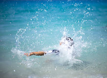 Unrecognizable girl splashing in crystal clear blue sea water. Stock Photos