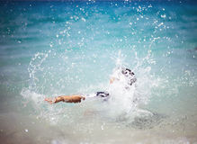 Unrecognizable girl splashing in crystal clear blue sea water. Summer holiday vacation fun concept. Retro colors Royalty Free Stock Photography
