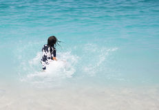 Unrecognizable girl splashing in crystal clear blue sea water. Royalty Free Stock Images