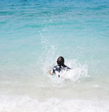 Unrecognizable girl splashing in crystal clear blue sea water. Summer holiday vacation fun concept. Retro colors Stock Photo