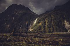 Unrecognizable guy near mountain and waterfall stock photo