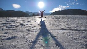 Unrecognizable guy standing on snowy meadow and raising hands up over the sun background. Young man enjoying freedom. During travel on sunny day. Holiday or stock video