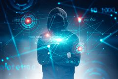 Unrecognizable hacker, binary code and hud. Unrecognizable hacker in black hoodie standing with crossed arms over dark blue background with immersive binary stock image