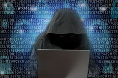 Unrecognizable hacker in front of computer – cyber crime concept. Unrecognizable hacker wearing a black hood to cover his face in front of computer stock photography