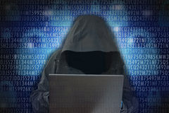 Unrecognizable hacker in front of computer – cyber crime concept. Unrecognizable hacker wearing a black hood to cover his face in front of computer stock photos