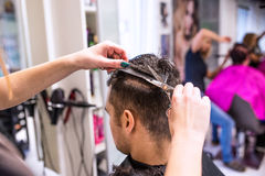 Unrecognizable hairdresser cutting hair of her young client. Stock Images