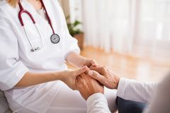 Health visitor and a senior man during home visit. Unrecognizable health visitor and a senior men during home visit. A nurse holding hands of a man Stock Image