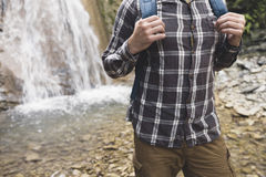 Unrecognizable Hiker Hands Holds Backpack Strap On Waterfall Background Hiking Journey Travel Concept. Tourist`s Hands Holds A Backpack Strap On Waterfall stock images