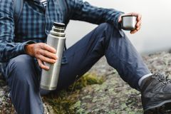 Unrecognizable Hiker Man Holding Thermos In His Hand. Hiking Adventure Tourism Concept. Unrecognizable young male traveler in a shirt, sitting on a rock and royalty free stock photo