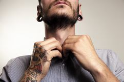 Unrecognizable hipster man with tattoos. Buttoning shirt , closeup shot Royalty Free Stock Images