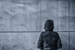 Unrecognizable hooded female person facing concrete wall as insu. Rmountable obstacle, young adult woman in urban surrounding confronting problems and Royalty Free Stock Images