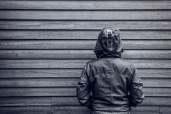 Unrecognizable hooded female person facing wooden wall. Monochromatic black and white image Royalty Free Stock Photo