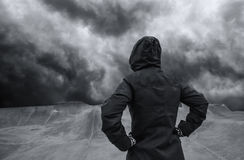Unrecognizable hooded person in empty skateboarding park Stock Images