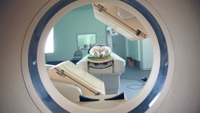 Unrecognizable hospital patient lying on MRI, tomograph, scanner, moving to and from the camera. Slider shoot.