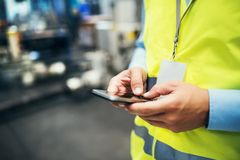 An unrecognizable industrial man engineer with name tag in a factory, using smartphone. royalty free stock photography