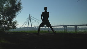 Unrecognizable jogger preparing for a jog in the morning. Silhouette runner warming up muscles legs before running. Urban city view in sunset. On the bridge stock video