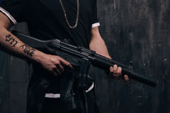 Unrecognizable killer with sniper rifle closeup. Studio shoot. Armed white gangster man with weapon and tattoo on dark background. Outlaw, ghetto, murderer Stock Photo