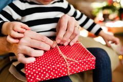 Unrecognizable little girl opening Christmas present. Royalty Free Stock Images